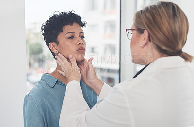 Buy stock photo Cropped shot of an attractive young female doctor examining a female patient in her office