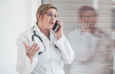 Buy stock photo Cropped shot of an attractive young female doctor speaking expressively on her cellphone while standing in her office