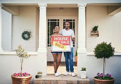 Buy stock photo Shot of a young couple standing in front of their new home with a sold real estate sign