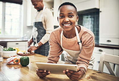 Buy stock photo Cropped portrait of an attractive young woman using a tablet in the kitchen while her husband cooks in the background