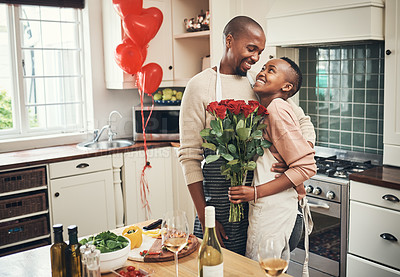 Buy stock photo Cropped shot of an affectionate young couple posing with a bunch of flowers in their kitchen on their anniversary