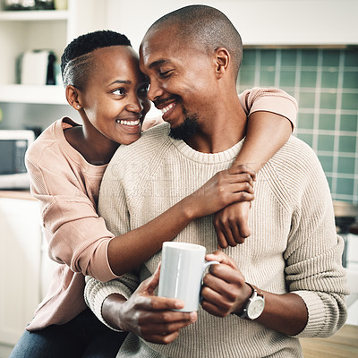 Buy stock photo Shot of a happy young couple drinking tea and spending time together at home