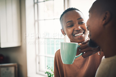 Buy stock photo Shot of a beautiful young woman drinking coffee and having a chat with her husband at home