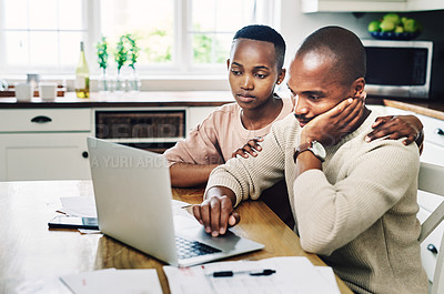 Buy stock photo Shot of a young couple looking stressed while going over their finances on a laptop at home