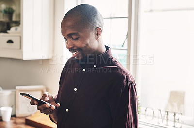 Buy stock photo Shot of a handsome young businessman using a cellphone  while working from home during the day