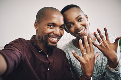 Buy stock photo Portrait of a happy newly engaged young couple taking selfies and showing their engagement rings at home