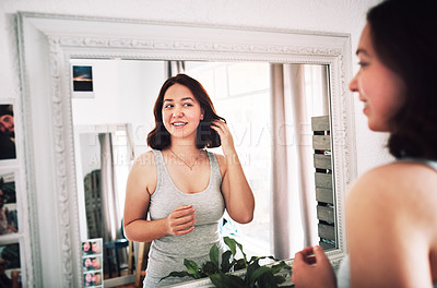 Buy stock photo Cropped shot of an attractive young woman admiring herself while standing in front of the mirror in her bedroom at home
