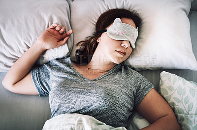 Buy stock photo High angle shot of an attractive young woman sleeping with a mask on her face in her bedroom at home