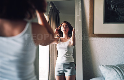 Buy stock photo Cropped shot of an attractive young woman inspecting her hair while standing in front of the mirror in her bedroom at home
