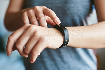 Buy stock photo Cropped shot of an unrecognizable woman standing alone in her home and setting her fitness tracker before working out