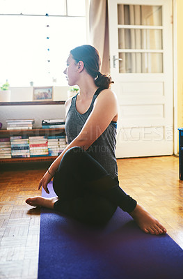 Buy stock photo Cropped shot of an attractive young woman sitting and holding a spinal half twist while doing yoga in her home