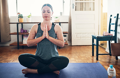 Buy stock photo Cropped shot of an attractive young woman sitting on a yoga mat and meditating alone in her home