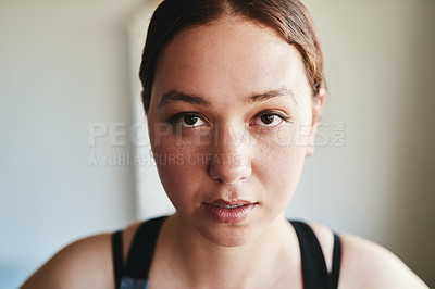 Buy stock photo Cropped shot of an attractive young woman standing alone and looking focused before working out in her home
