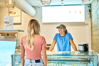 Buy stock photo Shot of a young man serving his customer in an ice cream parlour
