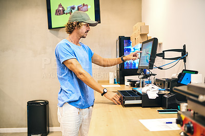 Buy stock photo Shot of a young man tallying up the sales for the day in his store
