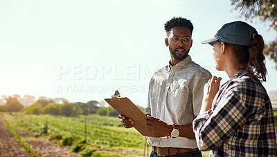 Buy stock photo Cropped shot of two young farmers looking over some paperwork while working on their farm