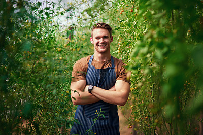 Buy stock photo Portrait of a handsome young farmer posing with his arms folded in the fields at his farm