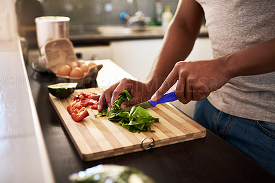 Buy stock photo Cropped shot of an unrecognizable man chopping vegetables while making a meal in his kitchen at home