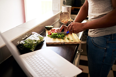 Buy stock photo Cropped shot of an unrecognizable man using a laptop while chopping vegetables in his kitchen at home