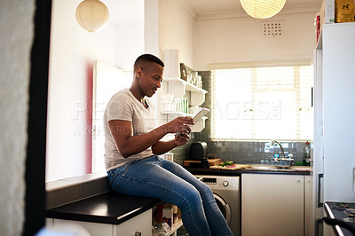 Buy stock photo Cropped shot of a handsome young man using a digital tablet while sitting on the kitchen counter at home
