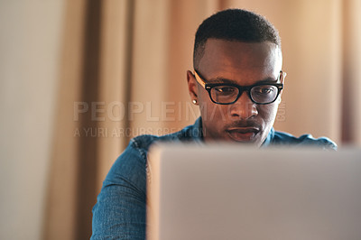 Buy stock photo Cropped shot of a handsome young businessman sitting alone in his home office and working on his laptop