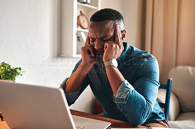 Buy stock photo Cropped shot of a handsome young businessman sitting alone in his office and suffering from a headache