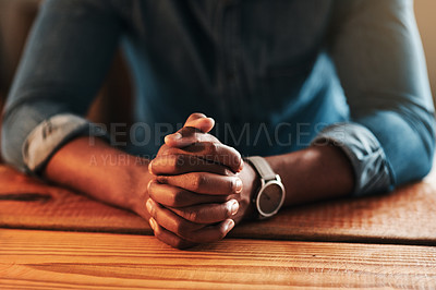 Buy stock photo Cropped shot of an unrecognizable businessman sitting with his hands together in his home office and praying