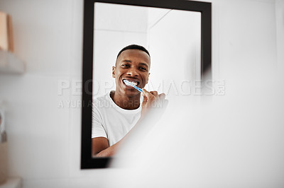 Buy stock photo Shot of a young man brushing his teeth while looking into the bathroom mirror