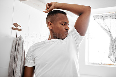 Buy stock photo Shot of a young man smelling his underarms while standing in the bathroom
