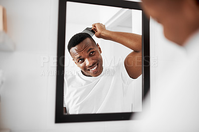 Buy stock photo Shot of a handsome young man combing his hair in the bathroom at home