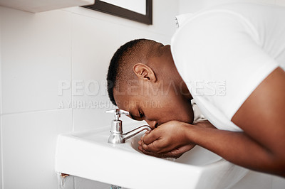 Buy stock photo Shot of a young man rinsing his mouth with water in the bathroom at home
