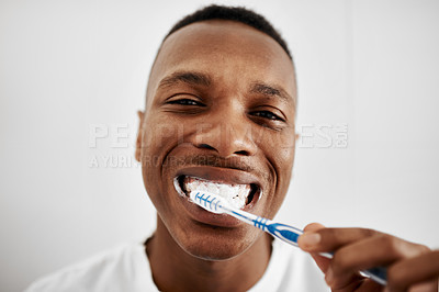 Buy stock photo Shot of a young man brushing his teeth in the bathroom at home