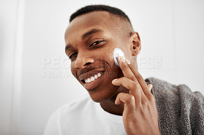 Buy stock photo Shot of a handsome young man applying moisturizer to his face at home