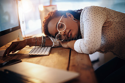 Buy stock photo Shot of a young businesswoman sleeping at her desk while working in an office at night