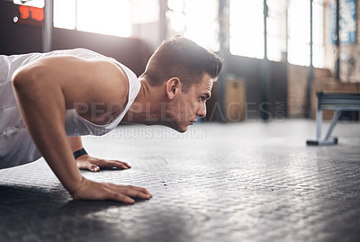 Buy stock photo Shot of a young man doing pushups in a gym