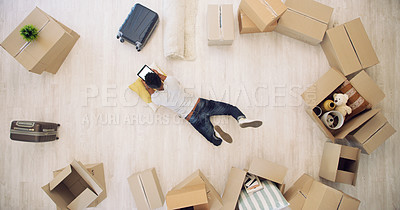 Buy stock photo High angle shot of a young man using a digital tablet while moving house
