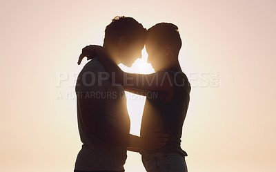 Buy stock photo Cropped shot of an affectionate young couple embracing each other while standing outdoors at sunset