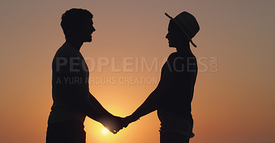 Buy stock photo Cropped shot of an unrecognizable couple holding hands while standing outdoors at sunset