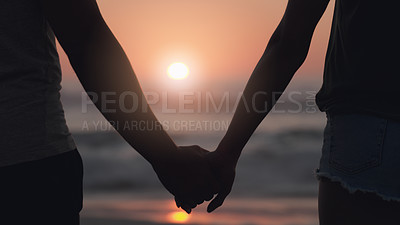 Buy stock photo Rearview shot of an unrecognizable couple holding hands while standing at the beach at sunset
