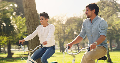 Buy stock photo Cropped shot of an affectionate young couple cycling together outdoors