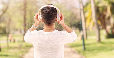 Buy stock photo Rearview shot of an unrecognizable woman listening to music on her headphones while walking through a park