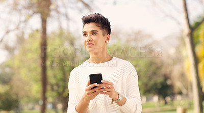 Buy stock photo Cropped shot of an attractive young woman looking thoughtful while using a smartphone in a park