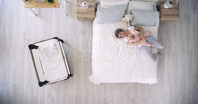 Buy stock photo High angle shot of a mother lying down on a bed with her baby daughter at home