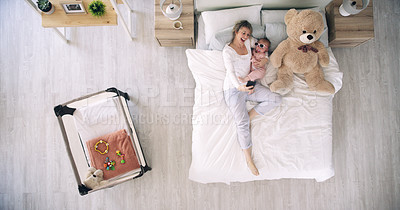 Buy stock photo High angle shot of a mother taking selfies with her baby daughter on a bed at home