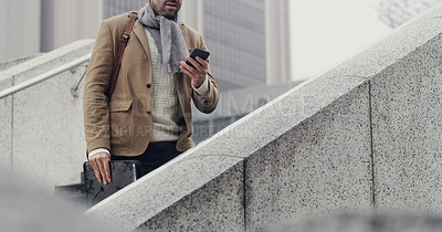 Buy stock photo Cropped shot of an unrecognizable businessman standing on a staircase and using his cellphone while on his way to work