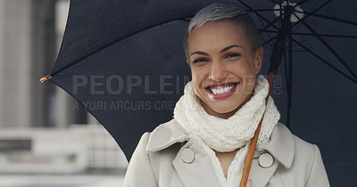 Buy stock photo Cropped shot of an attractive young businesswoman standing in the city alone and holding an umbrella