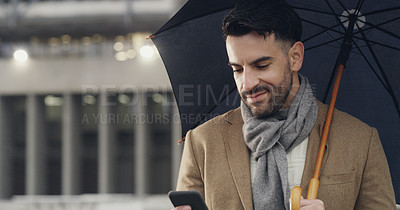 Buy stock photo Cropped shot of a handsome young businessman holding an umbrella and using his cellphone while walking through the city