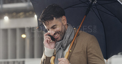 Buy stock photo Cropped shot of a handsome young businessman holding an umbrella and talking on his cellphone while walking through the city