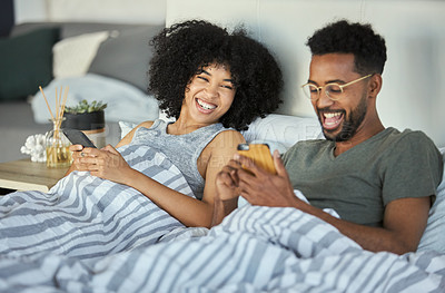 Buy stock photo Shot of a young couple using their cellphone while lying next to each other