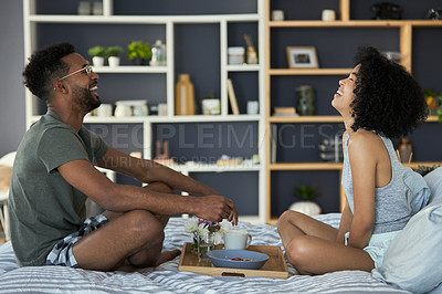 Buy stock photo Shot of a young couple having breakfast in their bedroom